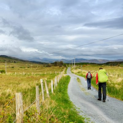 Two hikers ascend a trail on a cloudy day in the Killarney National Park. Hiking in County Kerry, Ireland.